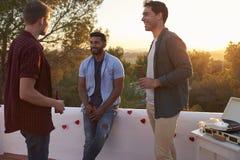 Trois amis masculins parlent à une partie sur un dessus de toit au coucher du soleil Photos libres de droits