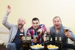 Trois amis masculins s'asseyant à la table avec de la bière Images stock