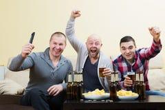 Trois amis masculins s'asseyant à la table avec de la bière Image stock