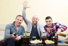 Trois amis masculins s'asseyant à la table avec de la bière Photographie stock libre de droits