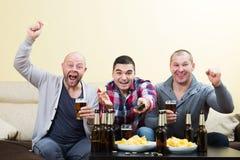 Trois amis masculins s'asseyant à la table avec de la bière Photo libre de droits