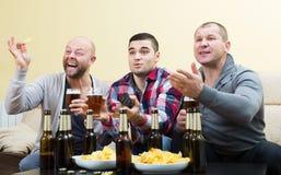 Trois amis masculins s'asseyant à la table avec de la bière Images libres de droits