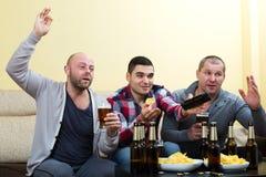 Trois amis masculins s'asseyant à la table avec de la bière Photographie stock