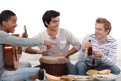 Trois amis mâles jouant des instruments Image stock