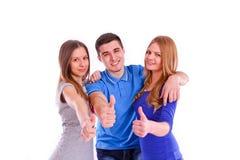 Trois amis montrant des pouces se connectent le dos de blanc Photo libre de droits