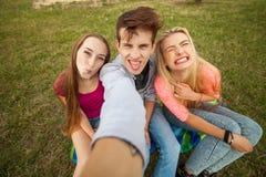 Trois amis observant prenant des photos avec le PC de comprimé en parc Photos libres de droits