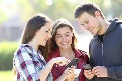 Trois amis partageant sur la ligne contenu dans la rue Photo stock