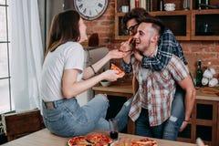 Trois amis partagent la pizza, ont l'amusement et rient Photo libre de droits