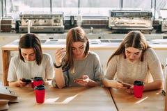 Trois amis passant en revue les réseaux sociaux Image stock