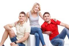 Trois amis posant sur le fond d'isolement Images libres de droits