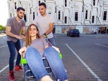 Trois amis poussant le chariot à achats avec une fille dans lui Images stock