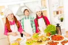 Trois amis préparant des hamburgers dans la cuisine Photos stock