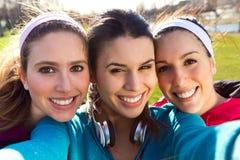 Trois amis prenant des photos avec un smartphone Images libres de droits