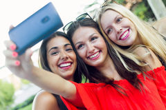 Trois amis prenant des photos avec un smartphone dans la rue Images libres de droits