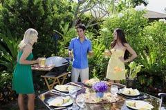 Trois amis prenant le déjeuner barbecue Photographie stock