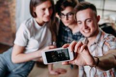 Trois amis prenant le selfie à un téléphone intelligent Photographie stock