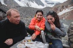 Trois amis prennent un casse-croûte sur une halte dans les montagnes pendant une hausse Brassez la tisane dans un thermos et man photo libre de droits