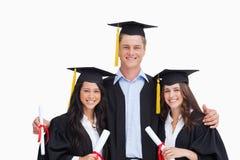 Trois amis reçoivent un diplôme de l'université ensemble Photographie stock libre de droits