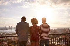 Trois amis regardant au-dessus de la ville image stock