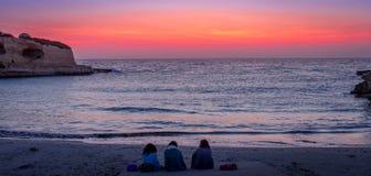 Trois amis regardant au lever de soleil Image libre de droits