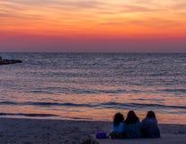 Trois amis regardant au lever de soleil Photos libres de droits
