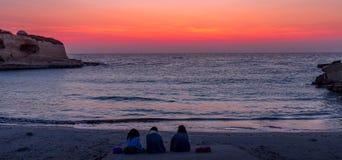 Trois amis regardant au lever de soleil Images libres de droits