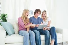 Trois amis regardant l'écran de la tablette dans le choc Photos stock