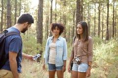 Trois amis regardant un téléphone portable Photos libres de droits