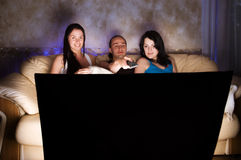 Trois amis regardent la TV Photo stock