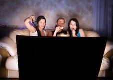 Trois amis regardent la TV Image libre de droits