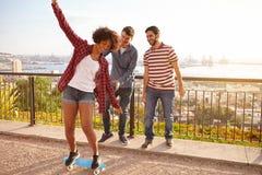 Trois amis riants et une planche à roulettes Photos libres de droits