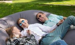 Trois amis riants heureux refroidissant dehors en parc sur a Image libre de droits