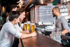 Trois amis s'asseyant à la barre et conservent la bière Quatre amis Photo stock