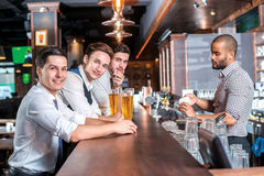 Trois amis s'asseyant à la barre et conservent la bière Quatre amis Photographie stock libre de droits