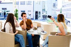 Trois amis s'asseyant au café tandis que l'un d'entre eux est bussy en prenant le selfie Image stock