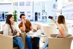 Trois amis s'asseyant au café tandis que l'un d'entre eux est bussy en prenant le selfie Image libre de droits