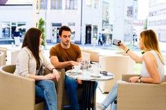 Trois amis s'asseyant au café tandis que l'un d'entre eux est bussy en prenant le selfie Photo stock