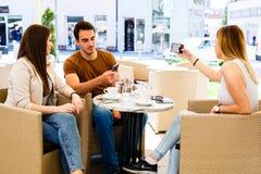 Trois amis s'asseyant au café tandis que l'un d'entre eux est bussy en prenant le selfie Images stock