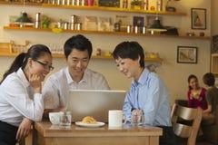 Trois amis s'asseyant dans le café, regardant vers le bas l'ordinateur portable Image libre de droits