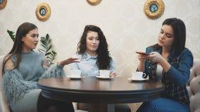Trois amis s'asseyant dans un café avec un téléphone intelligent et ayant une conversation drôle Bonnes filles avec le long beau  banque de vidéos