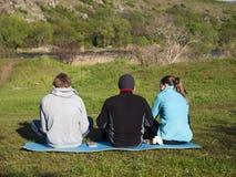Trois amis s'asseyant en nature Photographie stock libre de droits
