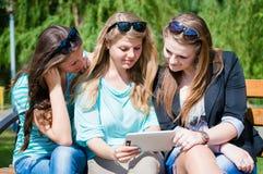 Trois amis s'asseyant en parc et regardant quelque chose sur le comprimé Photo stock