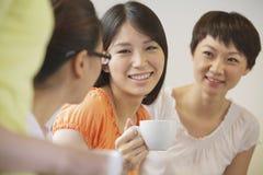 Trois amis s'asseyant et parlant dans un café, Pékin Images libres de droits