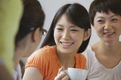Trois amis s'asseyant et parlant dans un café, Pékin Images stock