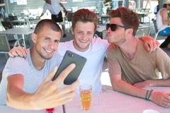 Trois amis s'asseyant faisant le selfie Photographie stock