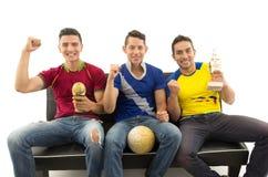 Trois amis s'asseyant sur l'interaction de sourire de port de chemises de sports de sofa avec l'appareil-photo jugeant le trophée Photos stock