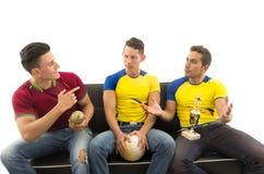 Trois amis s'asseyant sur l'interaction moqueuse de sourire de port de chemises de sports de sofa les uns avec les autres tenant  Images libres de droits