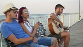 Trois amis s'asseyant sur le banc avec la mer comme fond et chantant avec une guitare clips vidéos