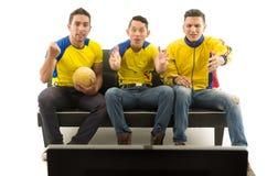 Trois amis s'asseyant sur le sofa utilisant les chemises de sports jaunes regardant la télévision avec enthousiasme, fond blanc,  Image stock