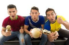 Trois amis s'asseyant sur les chemises de sports de port de sofa, tenant la boule et encourager criard de trophée à l'appareil-ph Images libres de droits